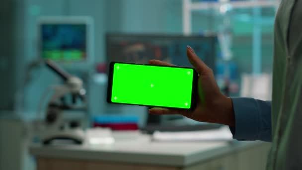 Detailní záběr vědec drží horizontální telefon se zelenou mockup