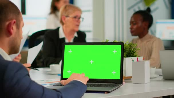 Back view of business man sitting conference desk using laptop with green screen