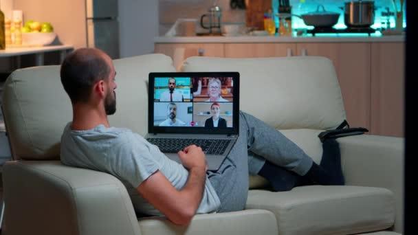 Pohodlný muž relaxovat na gauči při on-line obchodní konferenci