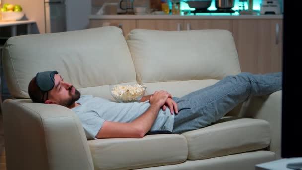 A férfi becsukja a szemét és elalszik a kanapén a nappaliban.