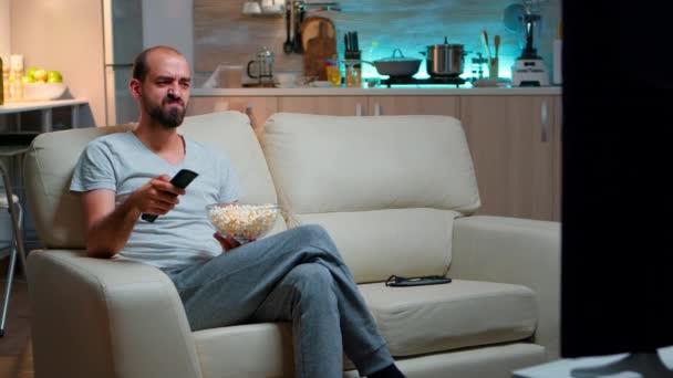 Unatkozó ember TV csatornát vált, popcornt tartott a kezében.