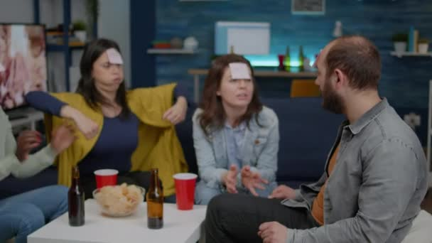 Smíšené rasy přátelé socializace během tvůrčí party při hraní legrační hádejte, kdo hra