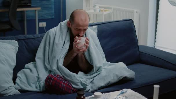 Mann mit kaltem Frösteln und Teetrinken