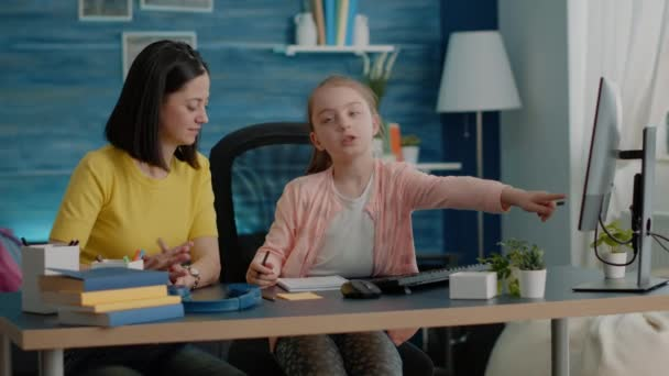 Schoolgirl and parent doing homework together with monitor