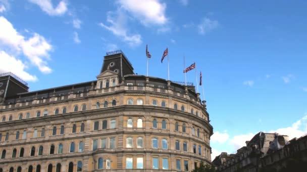Stará budova s britské vlajky, mával ve větru poblíž Trafalgar Square