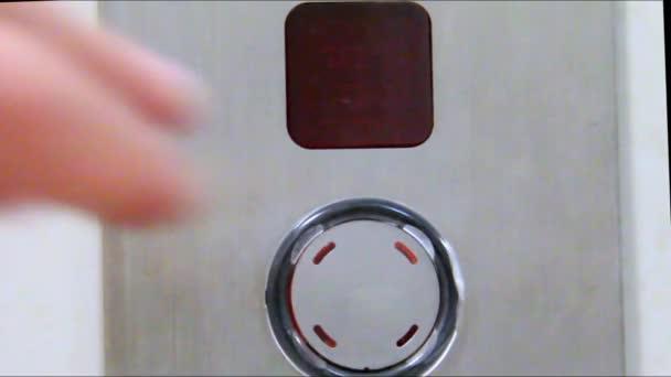 Zblízka muž prst stiskl tlačítko pro volání do výtahu