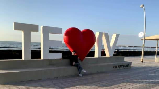 Tel Aviv, Israel - March 3, 2019: Woman on Tel Aviv love sign at the City old port on blue sky and Mediterranean Sea background,