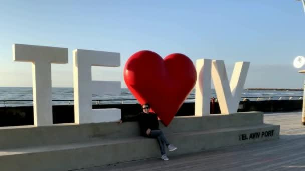 Tel Aviv, Izrael - 3. března 2019: Žena na milostném znamení Tel Avivu ve starém přístavu City na modrém nebi a pozadí Středozemního moře,