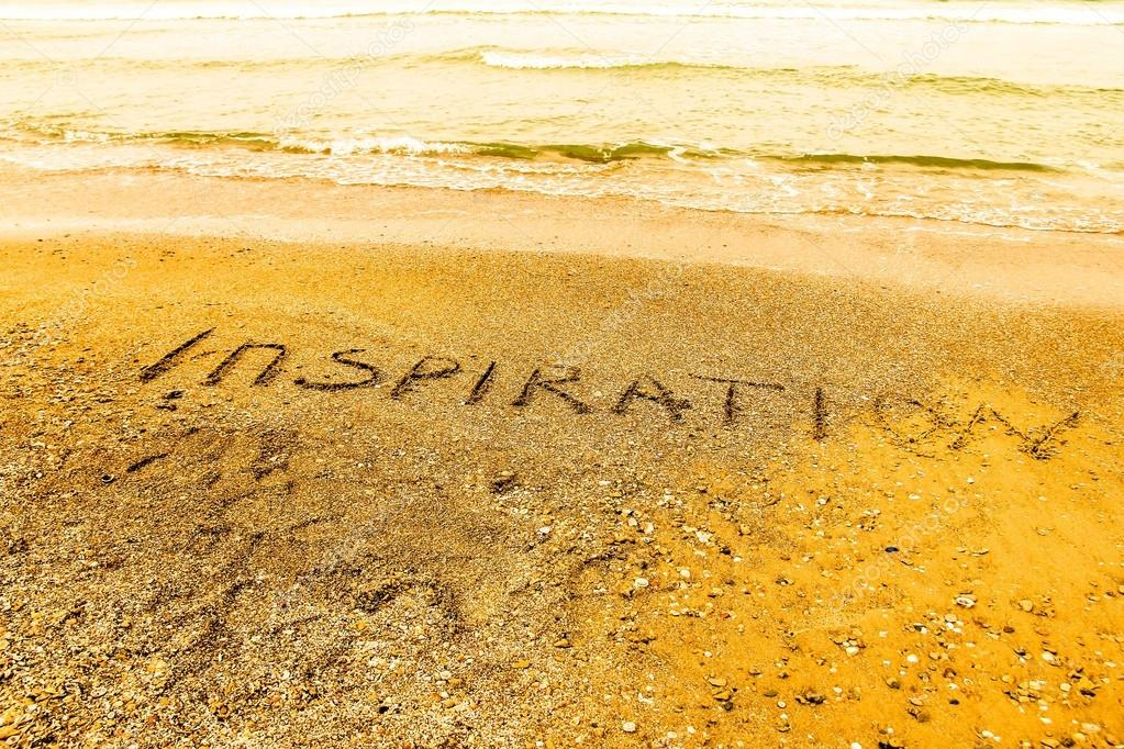 Inspiration. Creative motivation concept written in the sand at the beach.