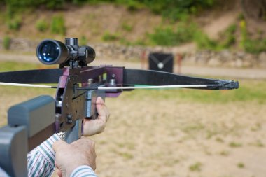 Man targeting with a scoped crossbow
