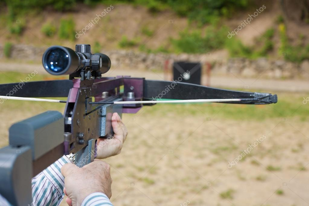 man targeting with a scoped crossbow stock photo andras csontos