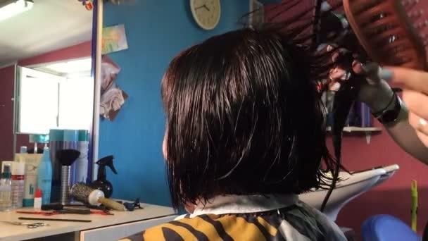 Fodrász szárad haj az ügyfél és a halom őket keresztül a hajszárító és a hajkefe.