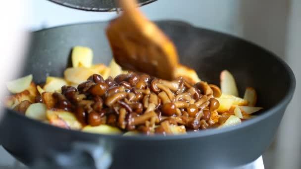 Smažené žampiony jsou přidány do pan smažené brambory a smíšené dřevěné špachtle.