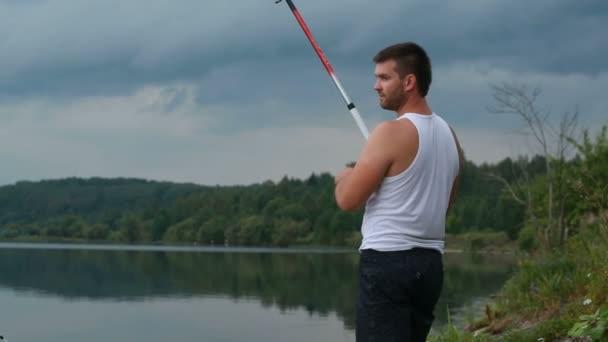 Mladý rybář s rybářským prutem na břehu jezera ve večerních hodinách