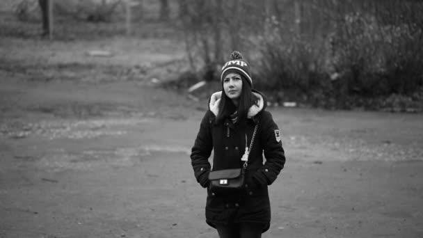 Osamělá dívka stojící na ulici v bundě a čepici