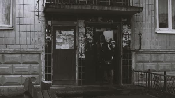Mladý muž a dívka z vchodu. Muž drží dva kufry