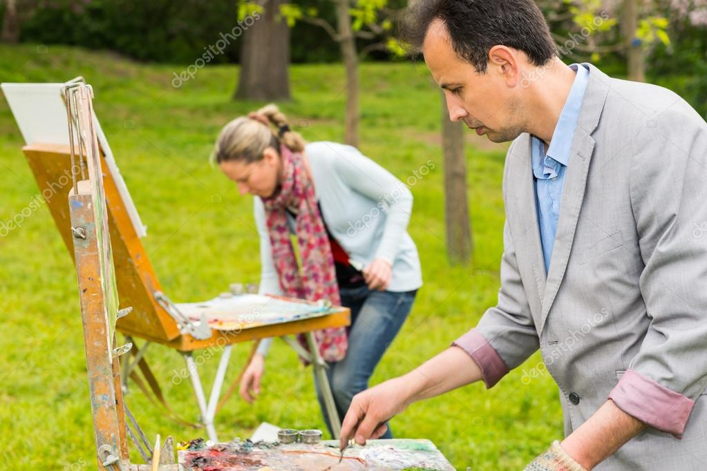 Two fashionable creative painters during an art class in a park