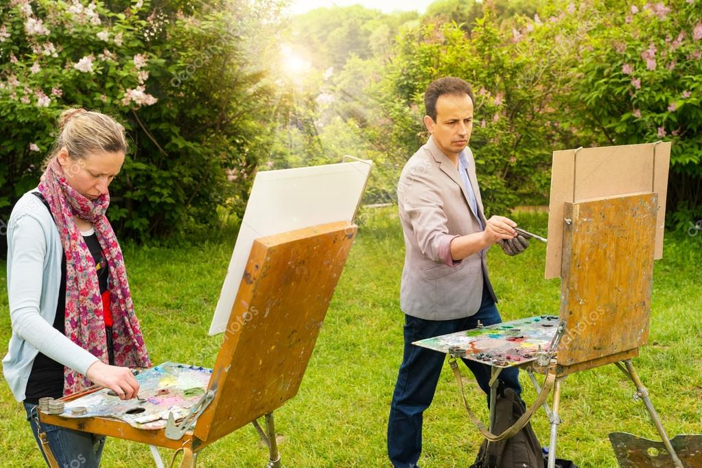 Two creative pensive painters painting in a garden