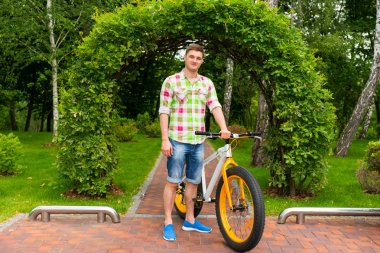 Handsome male with bike in a park