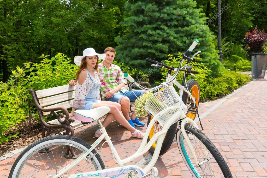 Young male and female sitting on bench near bikes