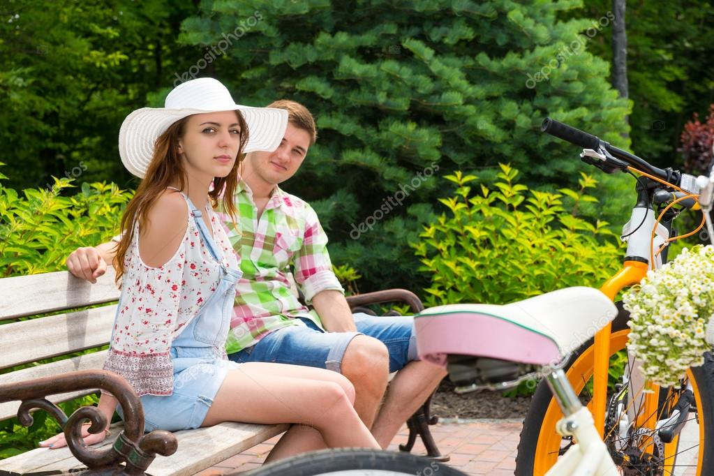 Attractive young couple sitting on bench near bikes in park