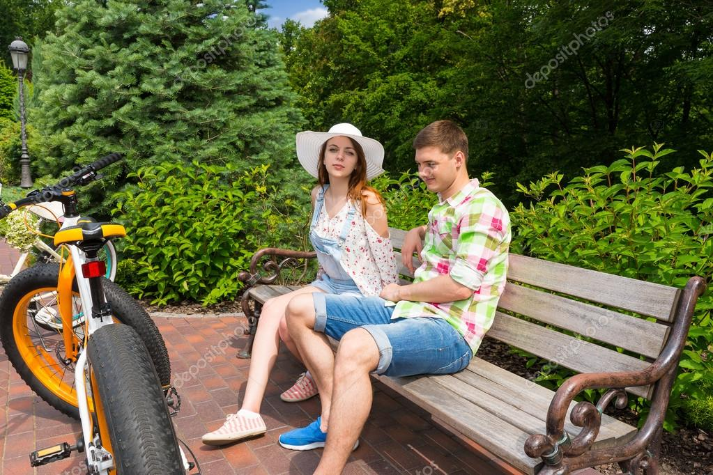 Young couple sitting on bench near bikes in park