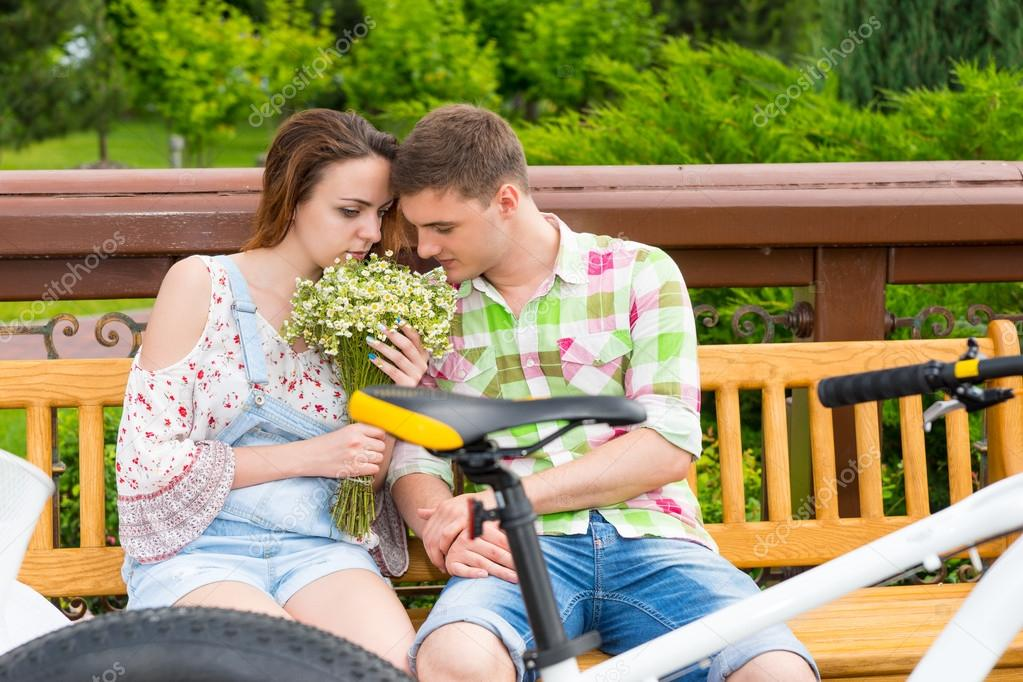Romantic couple sitting on a bench and smelling flowers in a par