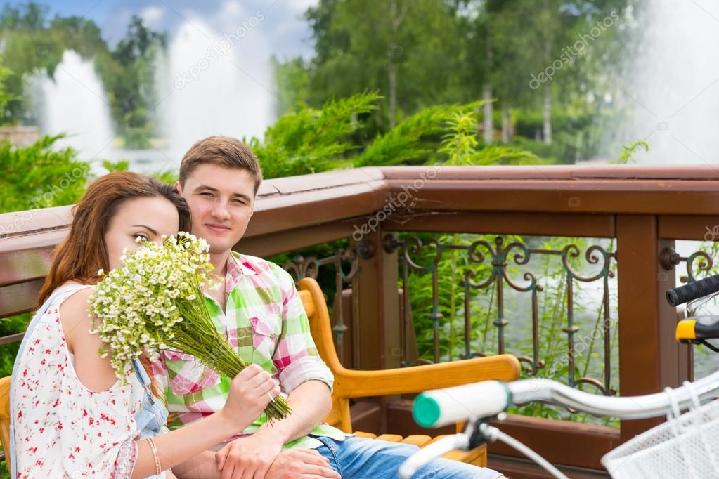 Youg female smelling flowers while sitting on a bench with a boy