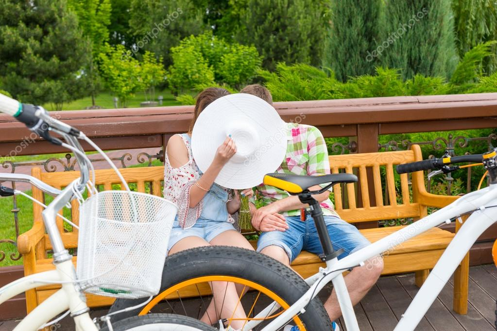 Boy and girl kissing hiding behind the hat while sitting on a be