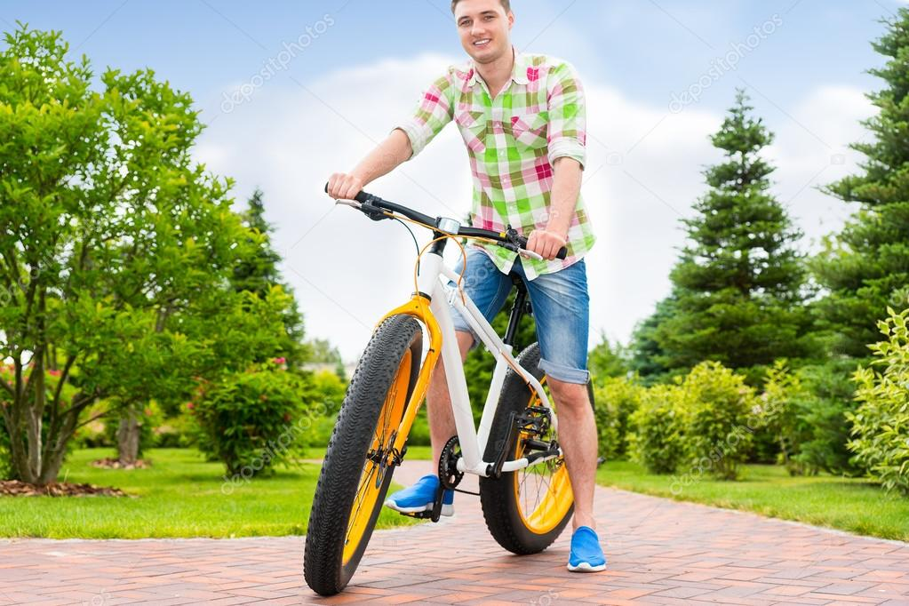 Fabulous handsome man sitting on his bicycle in a park