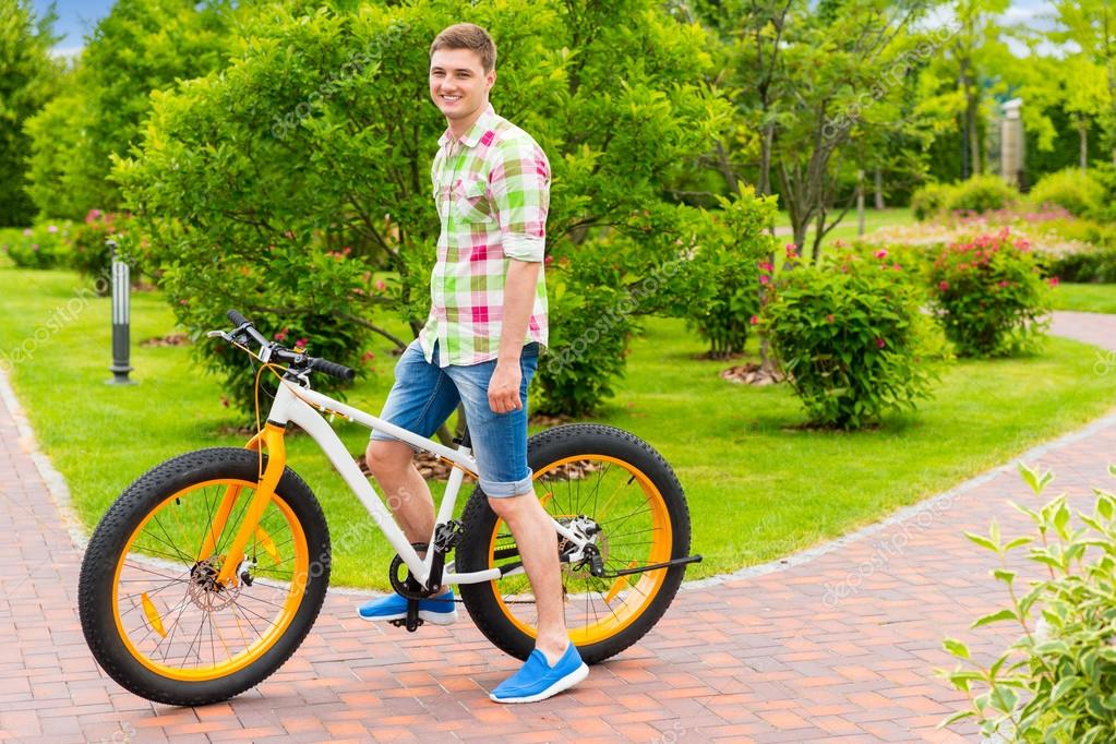 Happy smiling  guy sitting on his bicycle in a park