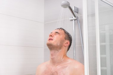 Young man with closed eyes taking a shower in the bathroom