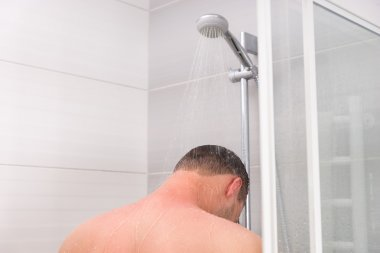 View from the back on a young man taking a shower