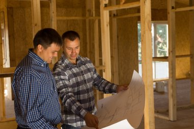 Two builders inside a half completed house