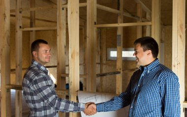 Two men shaking hands in a half constructed house