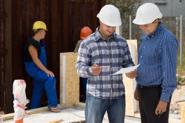 Engineer and architect wearing hardhats standing discussing paperwork on a construction site with builders working behind them stock vector