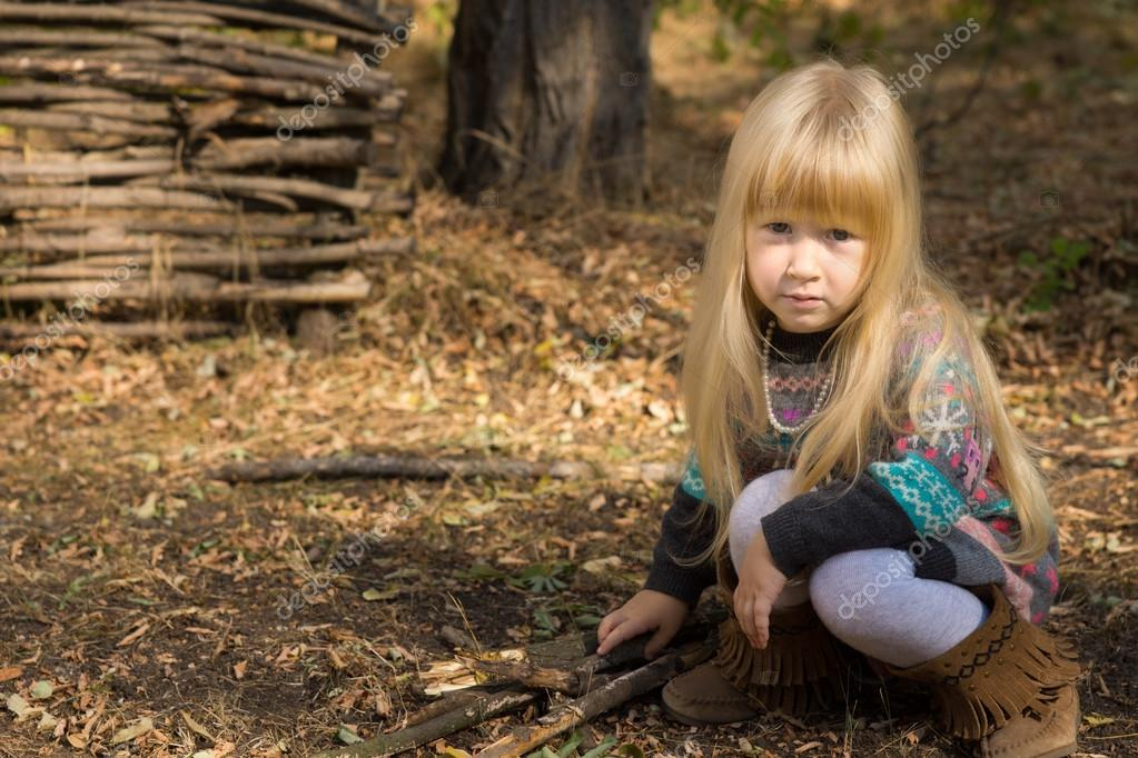 Pretty serious little blond girl playing outdoors