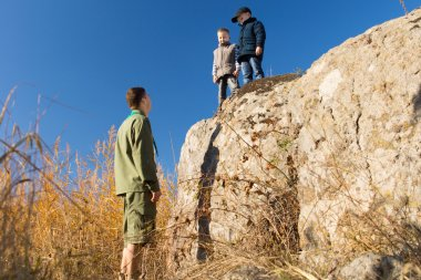 Male Scout on Ground Talking to Kids on Big Rock
