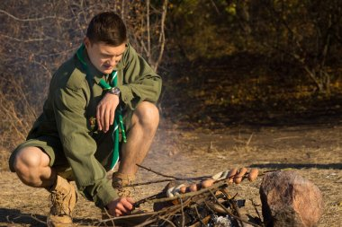 Young Male Scout Grilling Sausages at the Camp
