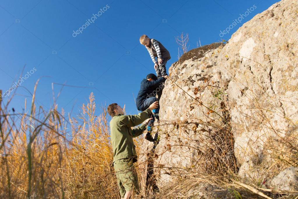Young man rock climbing with two boys