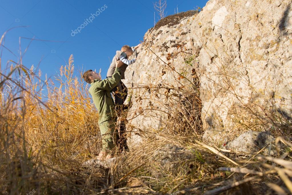 Man helping a young boy climb a rock
