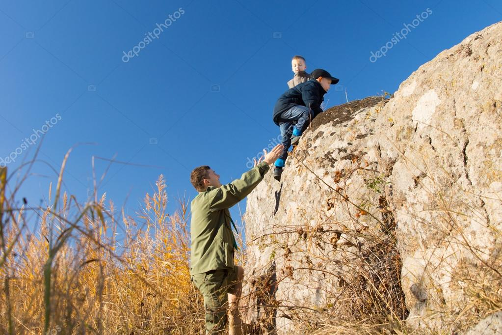 Young man helping two young boys climb a rock