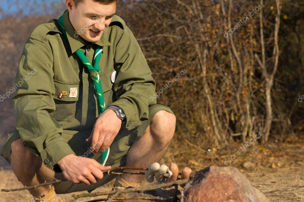 Young White Male Scout Cooking Sausages on Ground