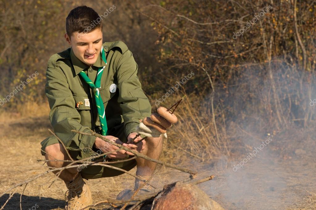 Young scout cooking his lunch over a fire