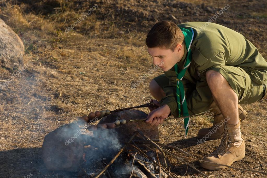 White Boy Scout Making Fire for Cooking at Camp