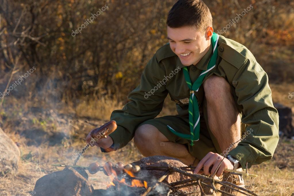 Young Boy Scout Cooking for Food on the Ground