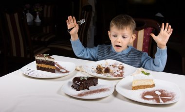 Happy little boy with an array of cake for dessert