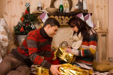 Young man and woman opening Christmas gifts