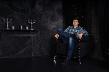 Man Sitting in High Back Chair in Haunted House