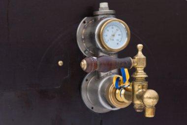 Brass gauge with a wooden handled valve